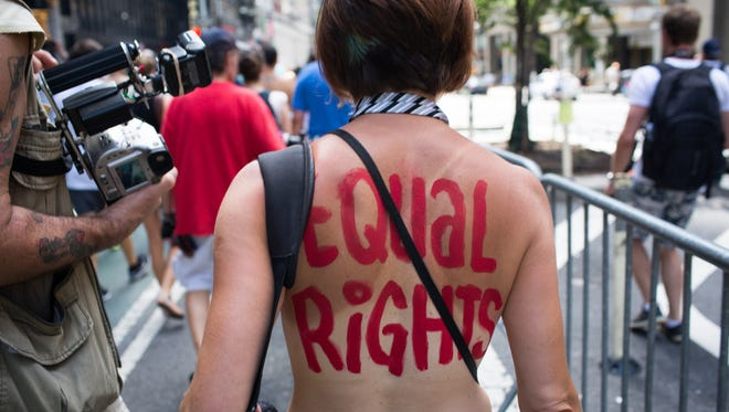 An activist marches in the protest march called the GoTopless Day Parade Sunday in New York.