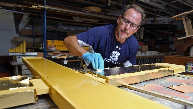 Lawrence Hoy burnishes artificial gold leaf on the cross that he is constructing in his studio in Port Chester Sept. 21, 2015. This is the cross that will serve as the backdrop to the alter that Pope Francis will say Mass from in Philadelphia this Sunday.
