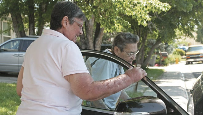 In this Friday, June 17, 2016, photograph, Lindsay Bethel opens the car door for Robert Green outside his residence in the Denver suburb of Aurora. Bethel gives Green rides to his weekly appointments at the University of Colorado Cancer Center as part of the American Cancer Society's Road to Recovery program that provides transportation to patients who need help to get to cancer treatments.