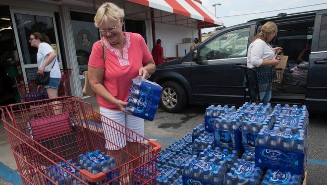 Debbie Hinners, left, a veteran of Hurricane Katrina, stocks up on bottled water on Tuesday, Sept. 5, 2017, at Pensacola's Apple Market.
