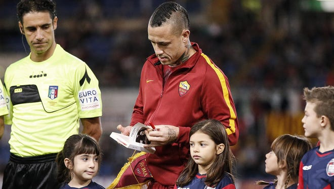 Roma's Radja Nainggolan holds a copy of 'The Diary of Anne Frank' before the Italian Serie A soccer match AS Roma vs FC Crotone at Olimpico stadium in Rome on Wednesday.