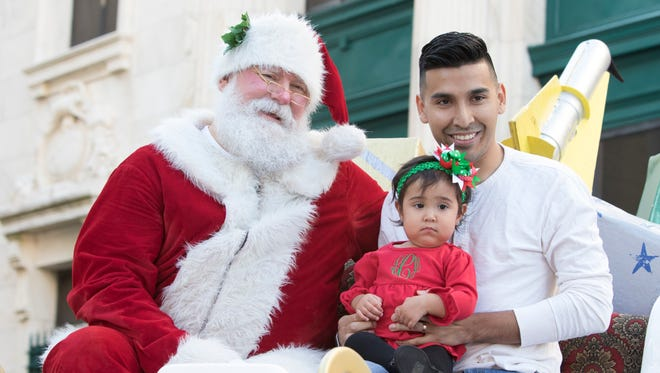 Jonathan Cardenas and his 13-month-old daughter Laila, of Perdido Key, pose with Santa before the Elf Parade in downtown Pensacola on Friday, November 24, 2017.