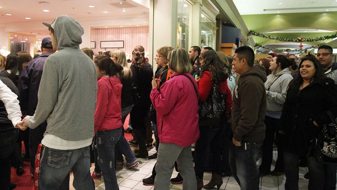 People stream through the doors as they open at Lancaster Mall.