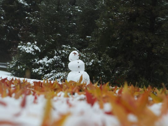 A snowman stands at the entrance to Whiskeytown National Recreation Area as snow covererd parts of the Redding area Thursday morning.