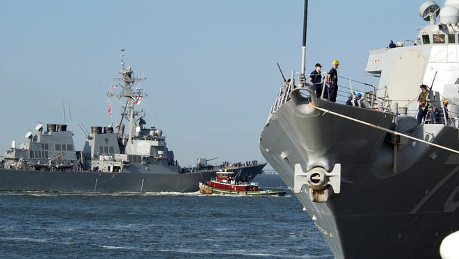 The guided missile destroyer USS Ramage, left, leaves port as  sailors aboard the USS Porter prepare to depart Norfolk Naval Station in Norfolk, Va., Tuesday Sept. 16, 2003.  The second fleet ordered 40 ships to sea to avoid the potential damage from Hurricane Isabel.