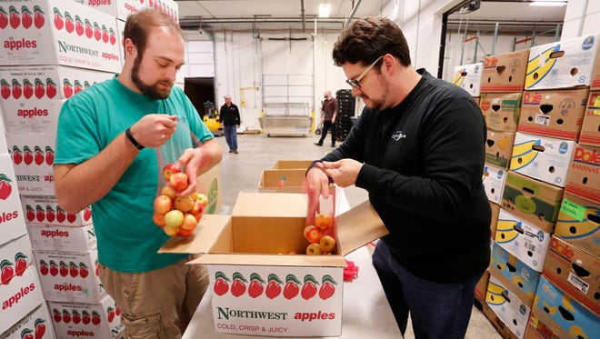 Volunteers Bryce Melton, left, and Bill English bag apples Thursday, November 2, 2017, at Food Finders Food Bank Warehouse, 1210 N. 10th Street in Lafayette. Food Finders, one of 21 United Way of Greater Lafayette agencies, might receive less funding if the campaign falls short of its $5.25 million goal.