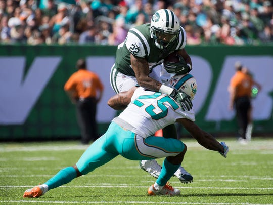 Jets running back Matt Forte (22) is tackled by Miami Dolphins cornerback Xavien Howard (25) during the second quarter at MetLife Stadium in Rutherford on Sunday, Sept. 24, 2017.