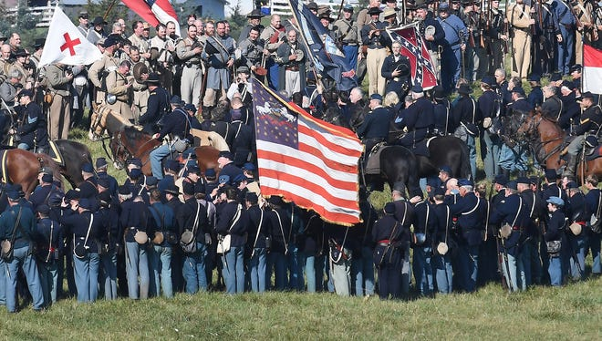 """Participants stand together following a reenactment of the Battle of Cedar Creek on Sunday in Middletown, Va. Reenactors chanted """"U.S.A."""" after their mock battle."""