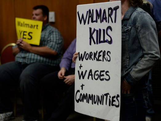Residents hold signs in favor and opposed to the proposed Walmart during the Green Bay City Council meeting at City Hall in downtown Green Bay on Tuesday, July 15, 2014. Evan Siegle/Press-Gazette Media