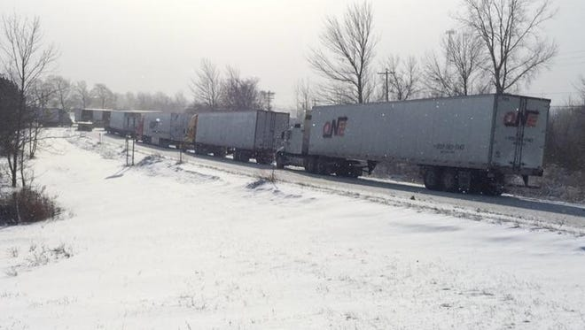 Trucks wait for the Thruway to open back up on a ramp near Le Roy.