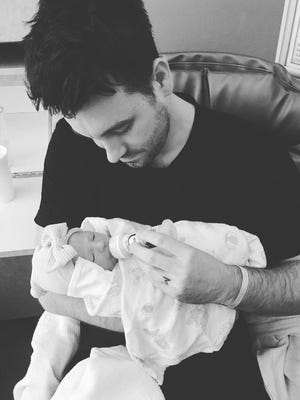 Christian music guitarist Nathan Johnson holds his newborn daughter Eilee. Johnson's wife, Megan, died Tuesday, June 27 from complications after child birth.
