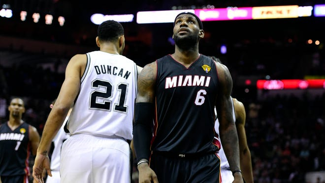 Miami Heat forward LeBron James (6) walks by San Antonio Spurs forward Tim Duncan (21) in game two of the 2014 NBA Finals at AT&T Center.