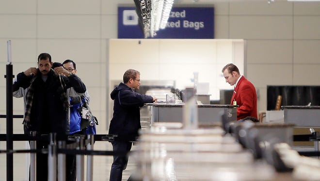 """American Airlines ticketing agent Cody Dear helps John Mejia check in for his flight to Miami at a nearly deserted terminal D at Dallas-Fort Worth International airport, Monday, Nov. 25, 2013. """"We would normally be slammed with the flight to Miami, but because of all the cancellations its been slow,"""" Dear said. Winter weather has caused travel disruptions throughout the area including the cancellation and delays of hundreds of flights. (AP Photo/Brandon Wade) ORG XMIT: TXBW106"""