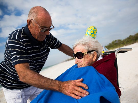 Russ Thomas covers Solveig Birkeland with a blanket to shield her from the sea breeze while celebrating her birthday on Friday, January 12, 2018 on Barefoot Beach in Bonita Springs.