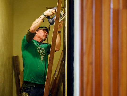 Independent contractor Scotty Grim works on the bathroom