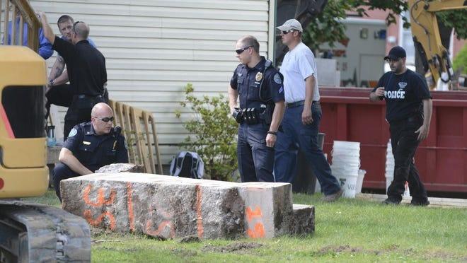 In this 2017 photo, police officers look over a slab of concrete pulled out of the basement of a home in Milton, Pa. Investigators hope cement taken from the Pennsylvania basement will solve the 1989 disappearance of Barbara Elizabeth Miller by determining if her remains were fed through wood chipper and then entombed there. Police said preliminary results showed the concrete contained wood chips and they're testing for the remains of Miller. (Robert Inglies/The Daily Item via AP)