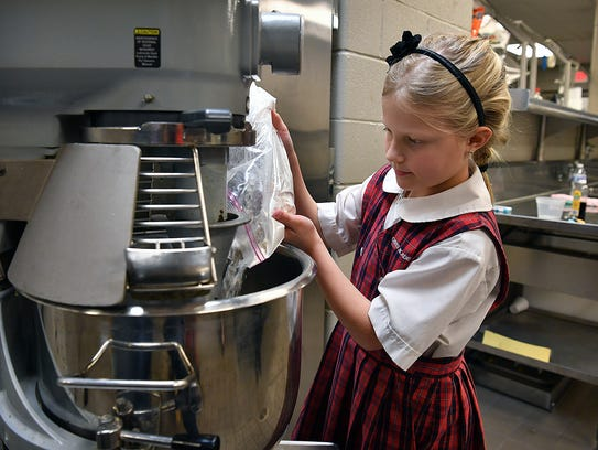 Wichita Falls third-grader Nikki Goodgion adds ingredients while making a batch of Valentine sugar cookies. Goodgion has started a cookie baking business and is learning about business plans, supply and demand and costs of supplies.