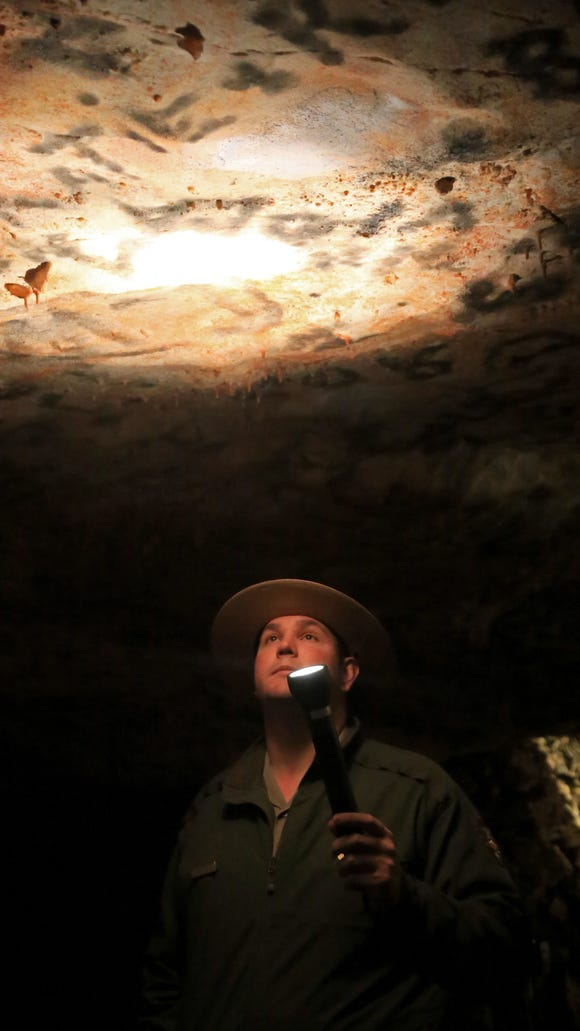 "Ranger Andrew Young shines a flashlight on the ""ceiling"""