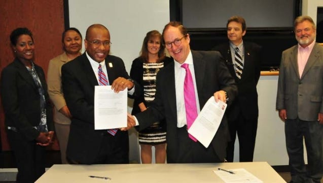 DSU President Harry L. Williams (l) and Rodney A Smolla, dean and professor of law, Widener University Delaware Law School, shake hands after the agreement signing. Behind them are (from left) Dr. Francine Edwards, interim dean of the College of Arts, Humanities and Social Sciences; Dr. Sandra DeLauder, assoc. provost; Barbara Ayars, Esq., assoc. dean of Del. Law admissions; Dr. Sam Hoff, director of the DSU Law Studies Program and Dr. Lee Streetman, professor of criminal justice.