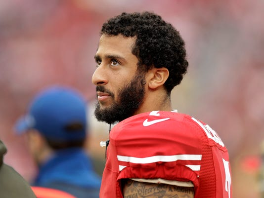 FILE - In this Nov. 8, 2015, file photo, San Francisco 49ers quarterback Colin Kaepernick stands on the field during an NFL football game against the Atlanta Falcons in Santa Clara, Calif. After months of trade talk and speculation, Kaepernick is still on the 49er's roster and due a hefty payday. The quarterback's $11.9 million 2016 contract became guaranteed at 1 p.m. local time Thursday, March 31, 2016, when the 49ers kept him on the roster. (AP Photo/Ben Margot, File)