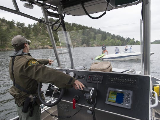 Ranger Trey Reilly instructs a boat to hold a flag in the air while a passenger floats in the water at Horsetooth Reservoir on Friday, June 23, 2017. Reilly patrols the 6-mile long body of water most weekends looking for boating violations and safety hazards.