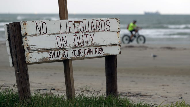 In this Friday, Sept. 29, 2017 photo, a cyclist passes a weathered sign along the beach in Port Aransas, Texas. Hurricane Harvey dealt a body blow to the beach town and wiped out the end of the lucrative summer season. Tourists are expected to stay away through the holidays, and even the possibility of getting back to business by spring break looks bleak. (AP Photo/Eric Gay)