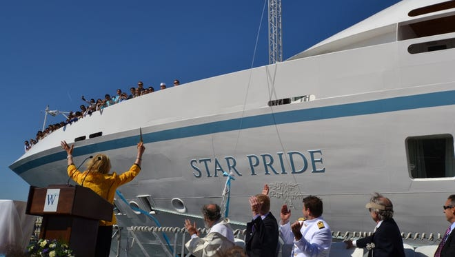Star Pride godmother Nancy Anschutz, left, and Windstar executives celebrate as a champagne bottle breaks against the hull of the 212-passenger Windstar vessel.