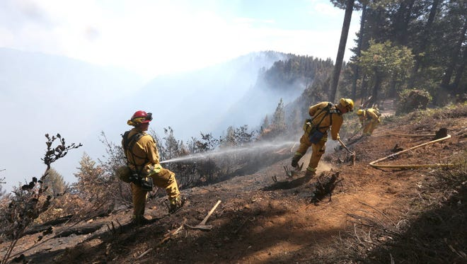 Firefighters hose down hot spots of the King Fire near Pollock Pines, Calif., Monday, Sept. 15, 2014.