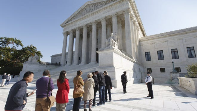 People wait to enter the Supreme Court on Monday.