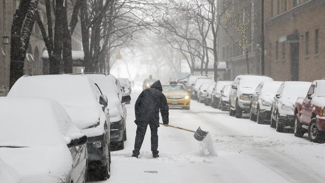 A man shovels snow into the street in Manhattan during January's cold weather in the U.S.