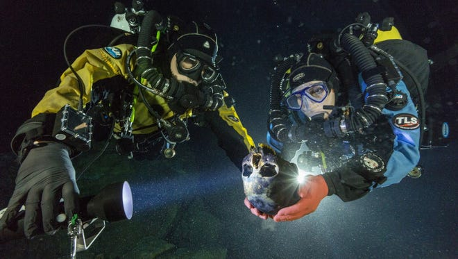 Divers Alberto Nava and Susan Bird transport the Hoyo Negro skull to an underwater turntable so that it can be photographed to create a 3-D model in an underwater cave in Mexico's Yucatan Peninsula. Thousands of years ago, a teenage girl fell into this deep hole and died. Now, her skeleton and her DNA are helping scientists study the origins of the first Americans. Her DNA links her to an ancient land bridge connecting Asia and North America, and suggests she shares ancestors with the modern native peoples of the Americas.
