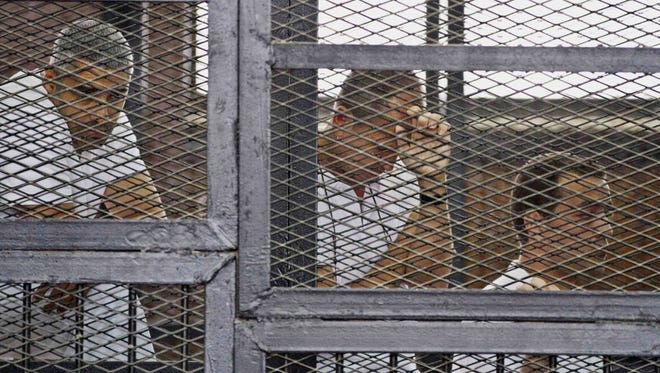 From left, Mohammed Fahmy, Peter Greste, and Baher Mohamed appear in a defendant's cage along with several other defendants during their trial on terror charges at a courtroom in Cairo. Photo is from May 15.