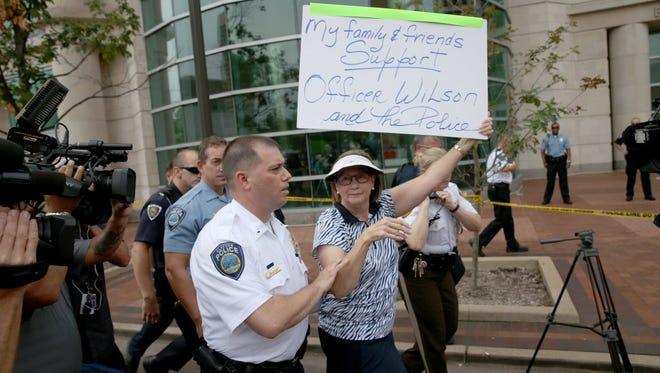 A police officer escorts a demonstrator away Wednesday in Clayton, Mo.