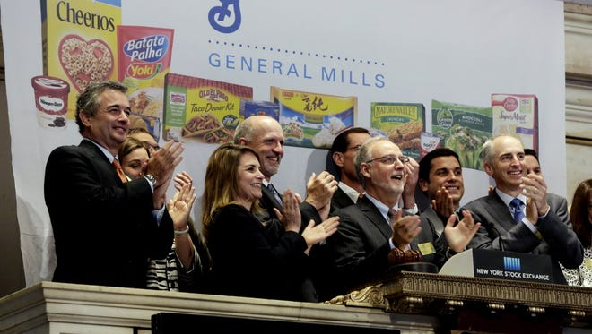 FILE - In this July 8, 2014 file photo, General Mills Chairman & CEO Kendall Powell, second from right, joins in applause as he rings the New York Stock Exchange Tuesday opening bell, July 8, 2014. The Minneapolis-based company, which last month announced a cost-cutting plan that will include a review of its manufacturing plants, is working to adapt its offerings as it grapples with the changing eating habits of Americans. (AP Photo/Richard Drew, File) ORG XMIT: NYBZ145