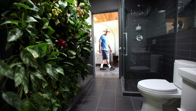 Ken Bernstein looks inside Team Alberta's bathroom, which features a living wall, at the Solar Decathlon 2013 on October 5, 2013 at Orange County Great Park in Irvine, Calif. Such living walls are gaining popularity in U.S. homes.