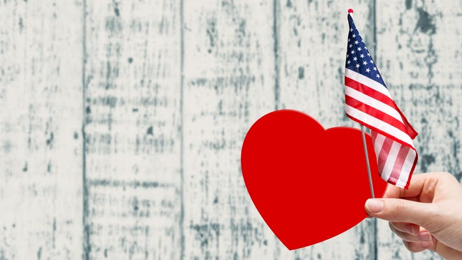 Hand holding red paper heart and USA flag