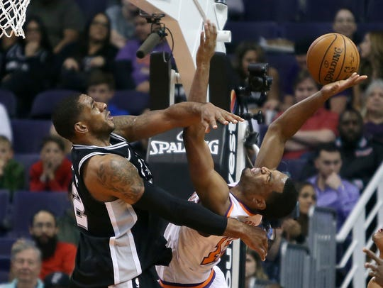 Spurs forward LaMarcus Aldridge blocks the shot of Suns forward T.J. Warren on Saturday in Phoenix.