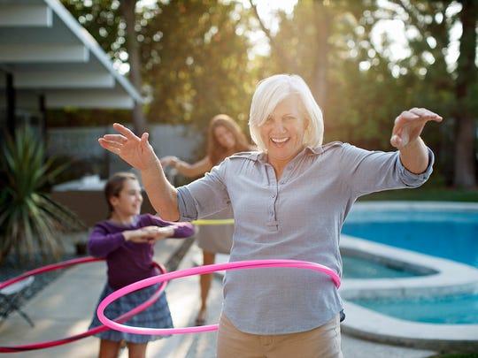 Older woman hula hooping in backyard