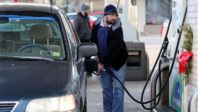 Noor Anwar, of Canton gases up at the BP gas station on Michigan Avenue and Mason Street in Dearborn.