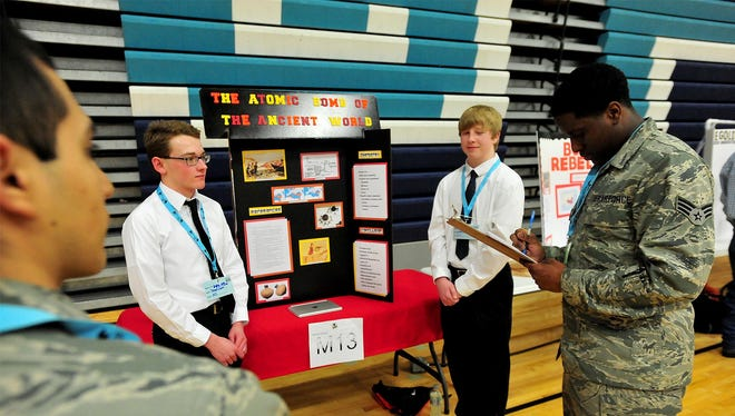 """Joseph Guter, left, and Griffin Austin present their WarFair project called """"The Atomic Bomb of the Ancient World"""" to Airman 1st Class Juan Garcia-Garcia, left, and Senior Airman James Jackson on Thursday in the Swarthout Fieldhouse."""