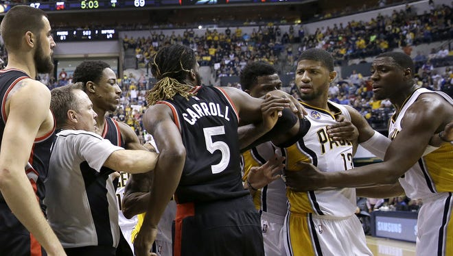 Indiana Pacers Paul George (13) and Toronto Raptors DeMarre Carroll (5) are separated after some pushing and shoving in the second half of their Eastern Conference first round playoff game Saturday, April 23, 2016, afternoon at Bankers Life Fieldhouse. The Pacers defeated the Raptors100-83.