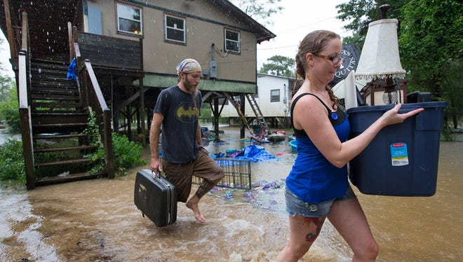 Getting out ahead of the flood, Michael Tramonte and Nikki Conger clear their possessions from their house on Watters Road, south of Hwy. 22 and east of Pontchatoula, La., ahead of the coming flooding Tangipahoa River as storms pound Tangipahoa Parish, Friday, Aug. 12, 2016.  Heavy downpours pounded parts of the central U.S. Gulf Coast on Friday, forcing the rescue of dozens of people stranded in their homes by waist-high water and leaving dead one man who was trapped by floodwaters. (Ted Jackson/NOLA.com The Times-Picayune via AP)