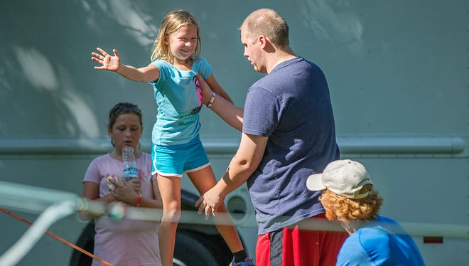 Maddie Funk, 6, tries slacklining with help balancing from Adam Daniels during ROC & ROW Festival on Labor Day, Broad Ripple Park, Indianapolis, Monday, September 5, 2016.