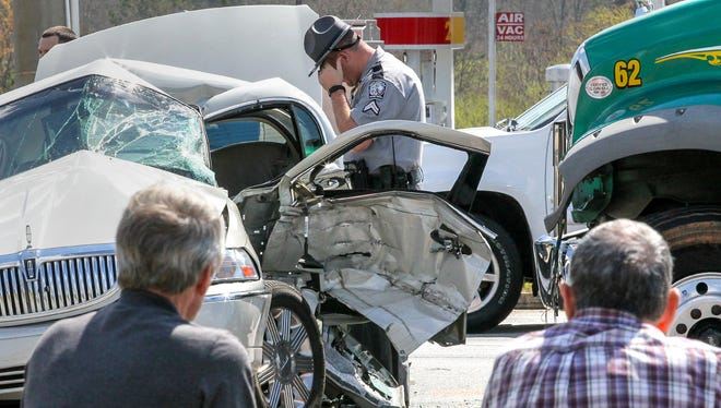 A South Carolina Highway Patrol officer looks over the scene of a wreck Friday afternoon at S.C. 24 and Whitehall Road. A Mack truck from Powell's Trash Services collided with a beige Lincoln Continental shortly after noon. The truck driver, left, was unharmed, but the driver in the car was taken to AnMed Health Medical Center by MedShore ambulance service.