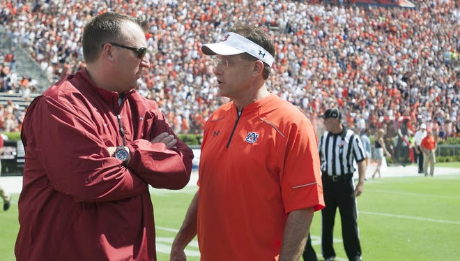 Arkansas Head Coach Bret Bielema, left, speaks with Auburn Head Coach Gus Malzahn before the start of the SEC football game between Auburn and Arkansas at Jordan-Hare Stadium in Auburn, Ala., on Saturday, Aug. 30, 2014.