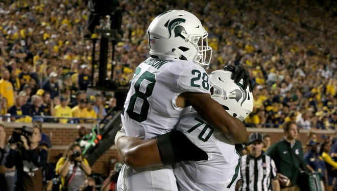 Michigan State running back Madre London (28) celebrates with teammate Tyler Higby in the end zone after scoring on a 16-yard screen pass against Michigan at Michigan Stadium in Ann Arbor on Saturday, Oct. 7, 2017.
