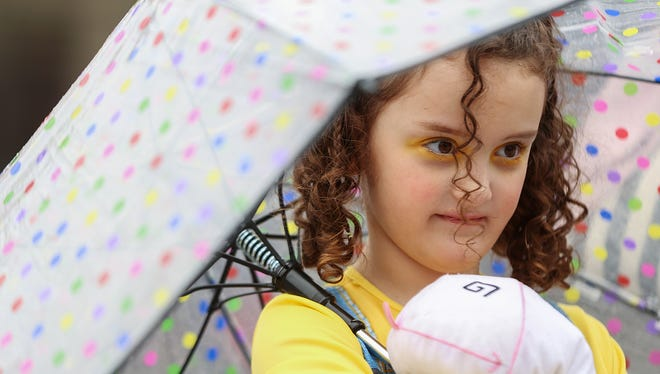 Amatullah Abdurrasheed, 6, held on tight to her stuffed unicorn under a polka dot umbrella that shielded her from rain in Downtown Indianapolis on April 29, 2017.