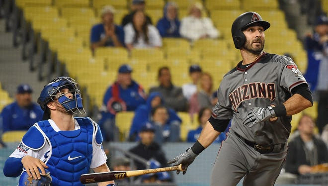 Los Angeles Dodgers catcher Kyle Farmer (17) looks on as  Arizona Diamondbacks third baseman Daniel Descalso (3) hits a three run home run in the 12th inning of the game at Dodger Stadium.
