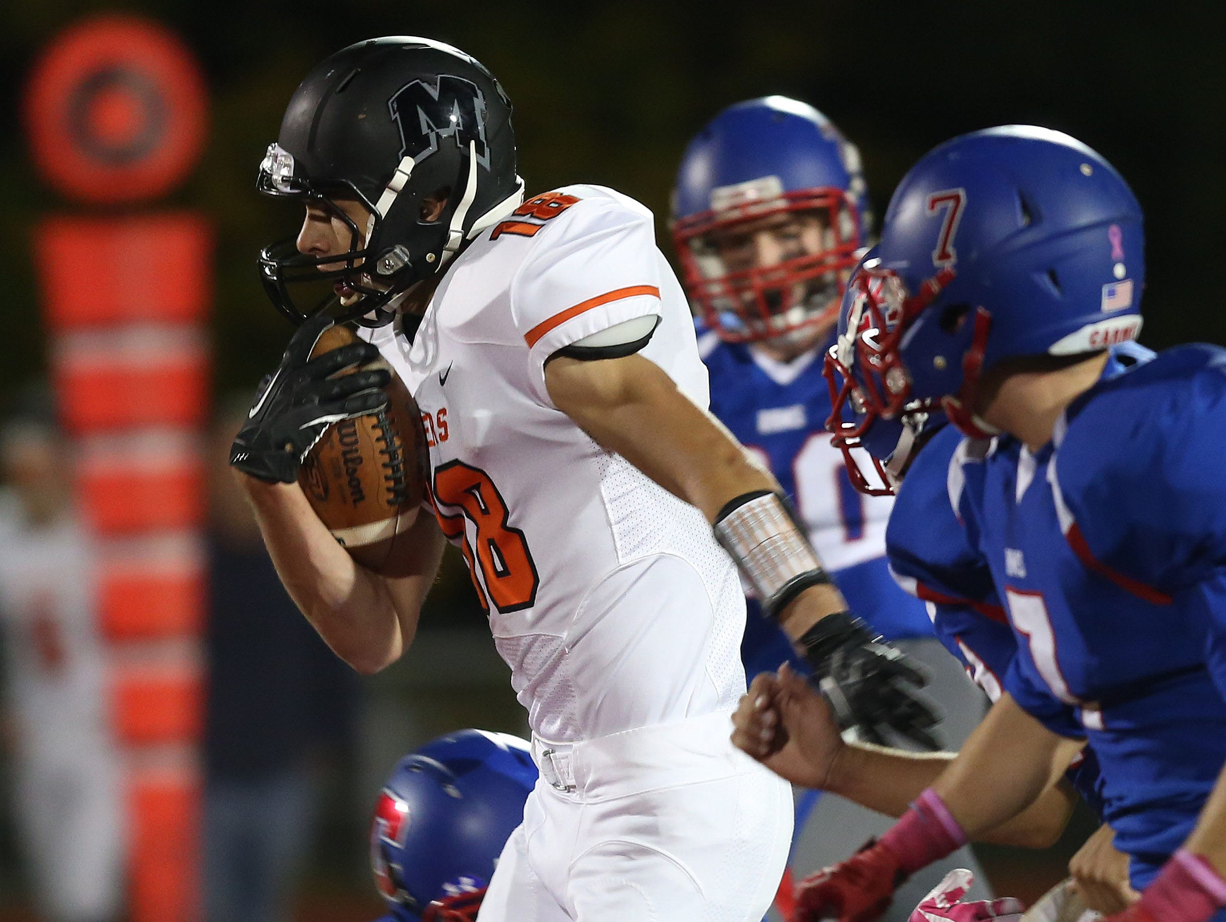 Mamaroneck's Jason Valastro (18) finds some running room in the Carmel defense on a first half run during a boys football playoff game at Carmel High School Oct. 16, 2015.