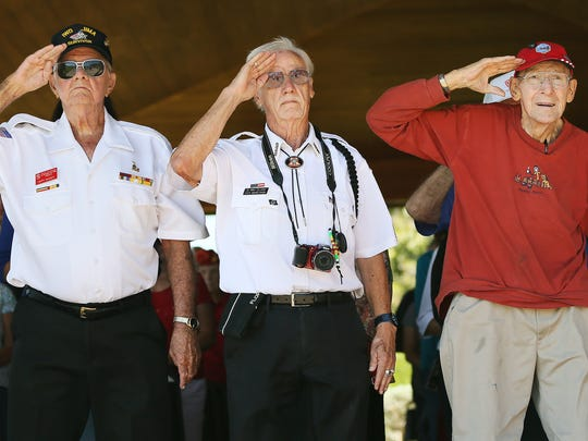 Pappy Wagner, left, D. Rex Clark and Lloyd Wolf honor the playing of TAPS Sunday during an Iwo Jima remembrance ceremony at the Veterans Memorial at Four Mile Cove Ecological Preserve in Cape Coral. Wagner and Wolf are Marines and Iwo Jima survivors. More than 100 people attended the annual event. US Marines captured the island of Iwo Jima from the Japanese Imperial Army during in a battle that raged from Feb. 19 to March 26, 1945.